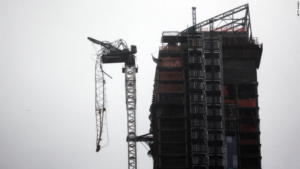 Part of a crane boom is seen hanging off a building under construction in Manhattan on Monday.