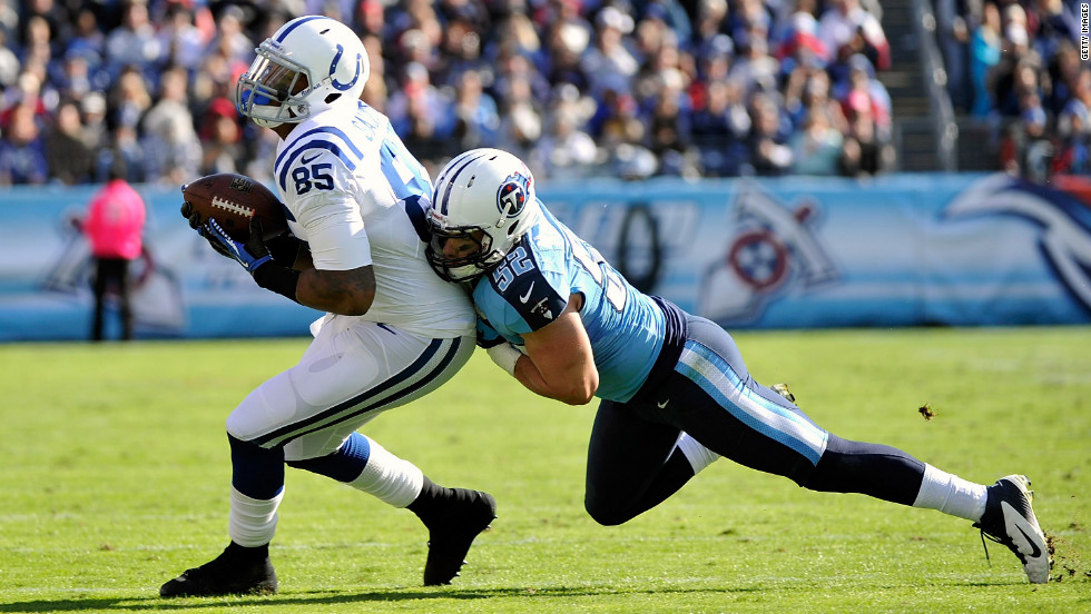 Colin McCarthy of the Tennessee Titans tackles Weslye Saunders of the Indianapolis Colts on Sunday in Nashville.