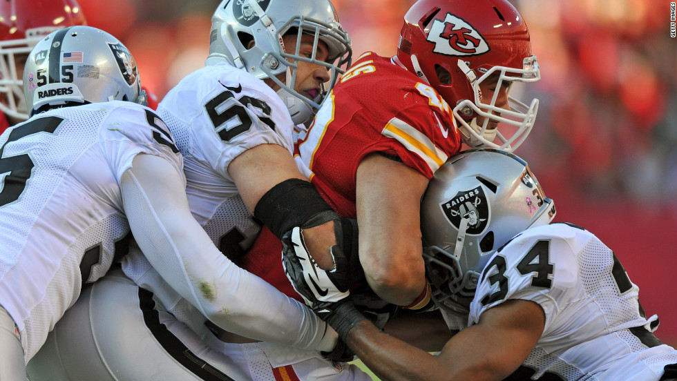 Oakland Raiders defenders No. 55 Rolando McClain, No. 56 Miles Burris and No. 34 Mike Mitchell tackle running back Peyton Hillis of the Kansas City Chiefs during the second quarter on Sunday in Kansas City, Missouri. The Raiders defeated the Chiefs 26-16.
