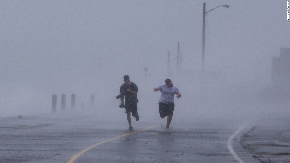 Two men run down Foster Avenue while dodging high winds and waves from the storm on Monday in Marshfield, Massachusetts.
