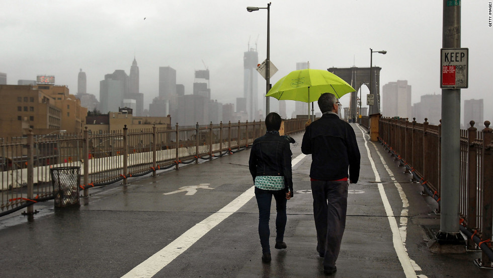 People take a Tuesday morning walk on the Brooklyn Bridge, which remains closed to traffic after the city awakened to the storm damage.