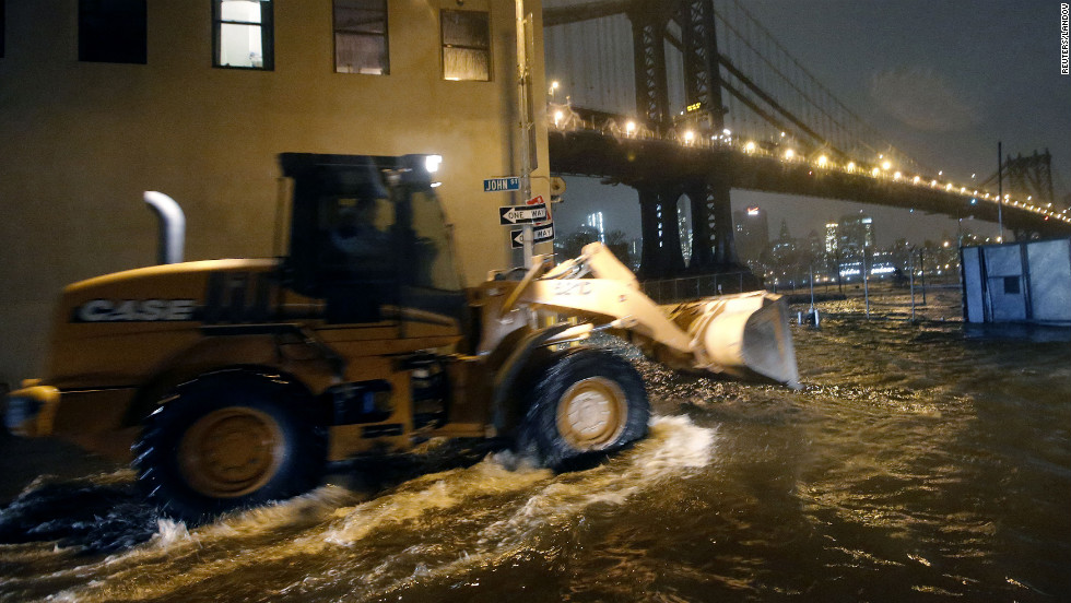 A construction vehicle drives through flooded streets in Brooklyn on Monday as Sandy makes its way north.