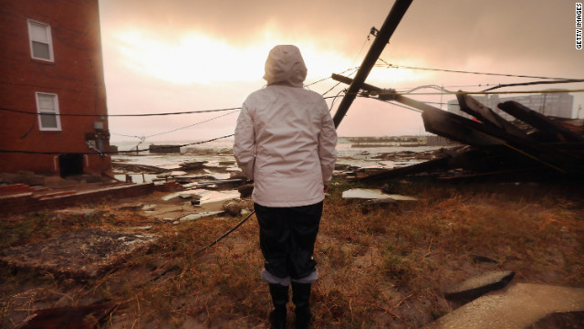 ATLANTIC CITY, NJ - OCTOBER 30:  Resident Kim Johnson inspects the area around her apartment building (L) which flooded and destroyed large sections of an old boardwalk, on October 30, 2012 in Atlantic City, New Jersey. Johnson fled the area when the water began to rise yesterday.  The storm has claimed at least 16 lives in the United States, and has caused massive flooding accross much of the Atlantic seaboard. US President Barack Obama has declared the situation a 'major disaster' for large areas of the US East Coast including New York City. (Photo by Mario Tama/Getty Images)