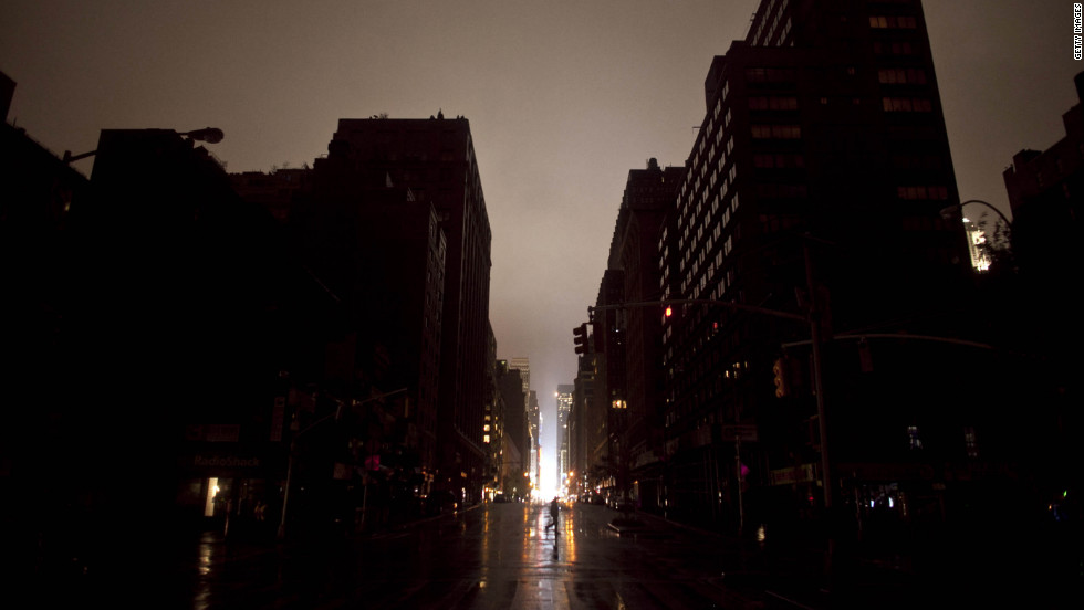 A pedestrian walks across a New York street where the power was out late Monday. The storm surge set records in Lower Manhattan, where flooded substations caused a widespread power outage.