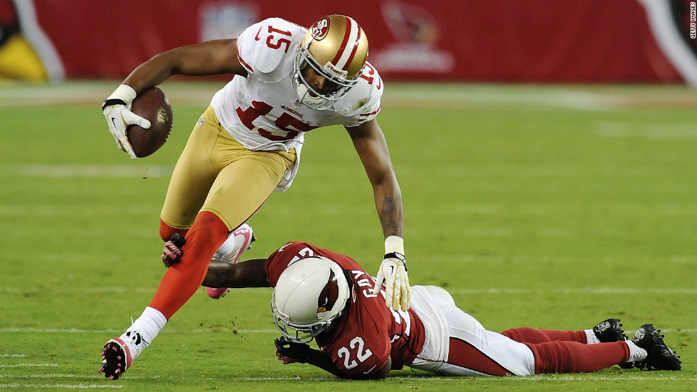 Michael Crabtree of the 49ers runs with the ball as William Gay of the Cardinals attempts to make a tackle.