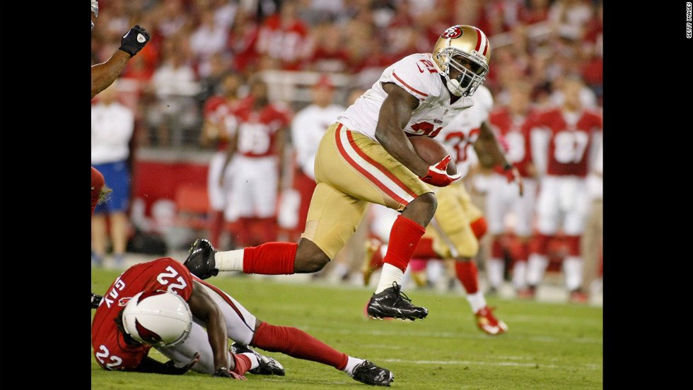 Frank Gore of the San Francisco 49ers leaps over William Gay of the Arizona Cardinals on a first-down run during the first quarter Monday.