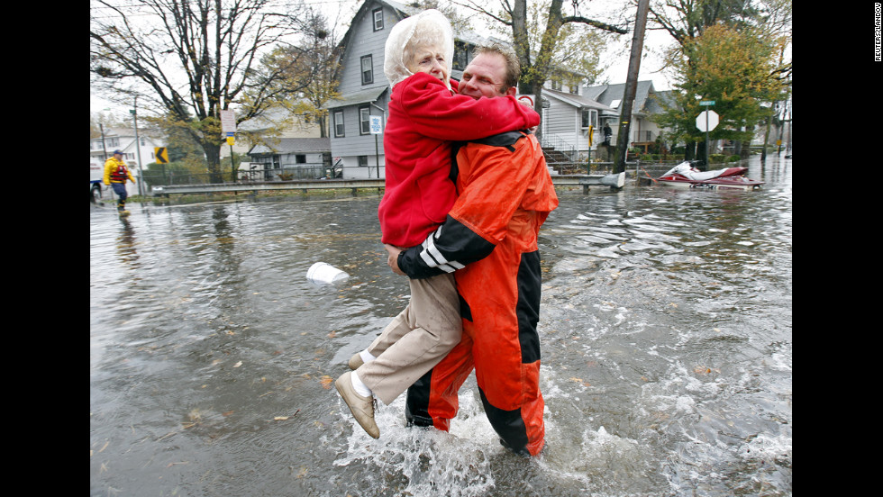 An emergency worker carries a resident through floodwaters in Little Ferry, New Jersey, on Tuesday.