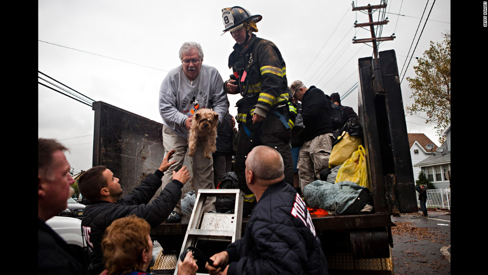 A New York City man hands a dog to first responders while being evacuated on Tuesday.