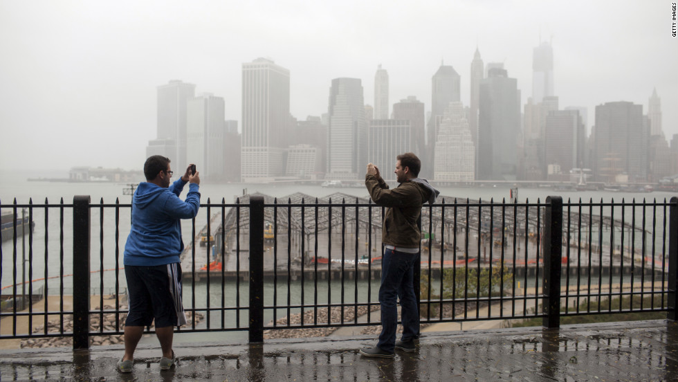 Two people shoot video along Brooklyn Heights' Promenade on Monday as Sandy approaches landfall.
