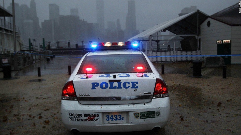A police car looks out over Manhattan from near the Brooklyn Bridge as Sandy begins to affect the area on Monday.