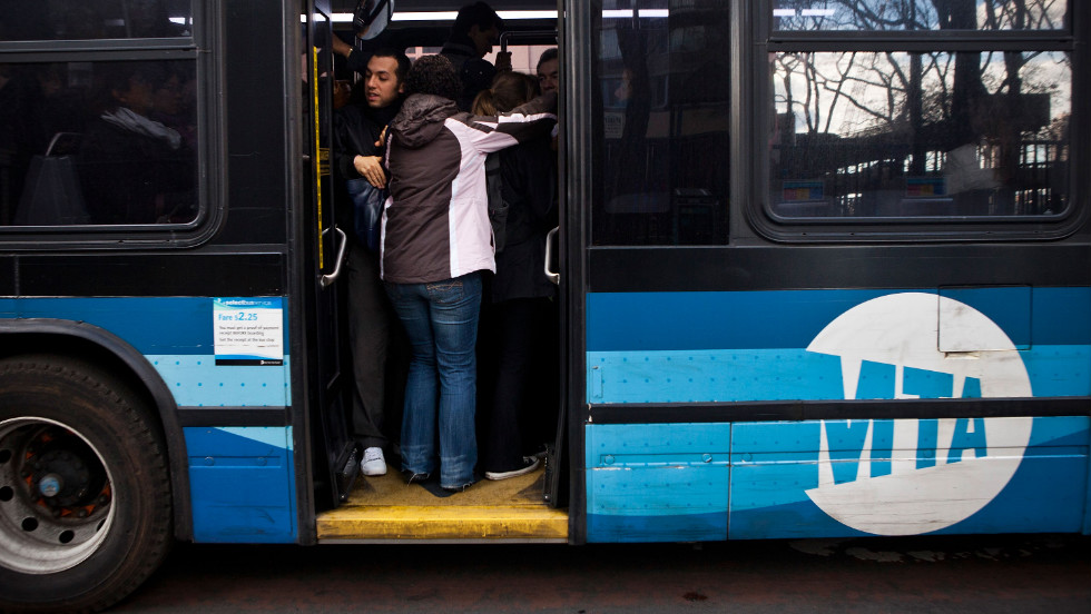 People attempt to squish into a crowded bus on First Avenue in New York on Wednesday.