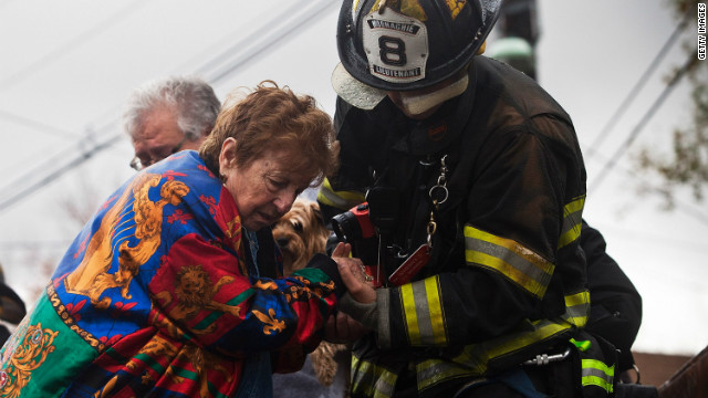 A woman is helped down from a truck by an emergency responder after being evacuated in Little Ferry, New Jersey.