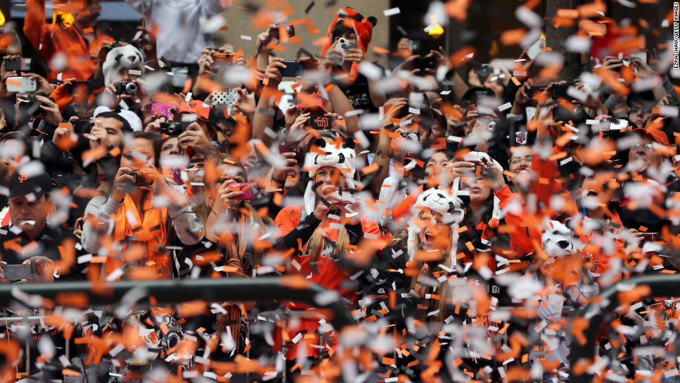 Fans line the street. The team's colors are orange and black, and the parade fell on Halloween.