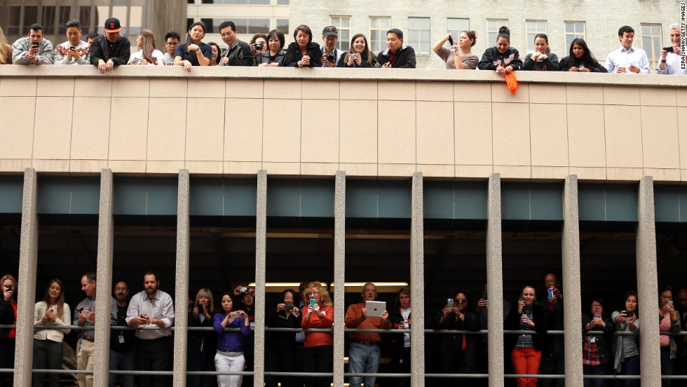 Giants fans watch from a building along the parade route.
