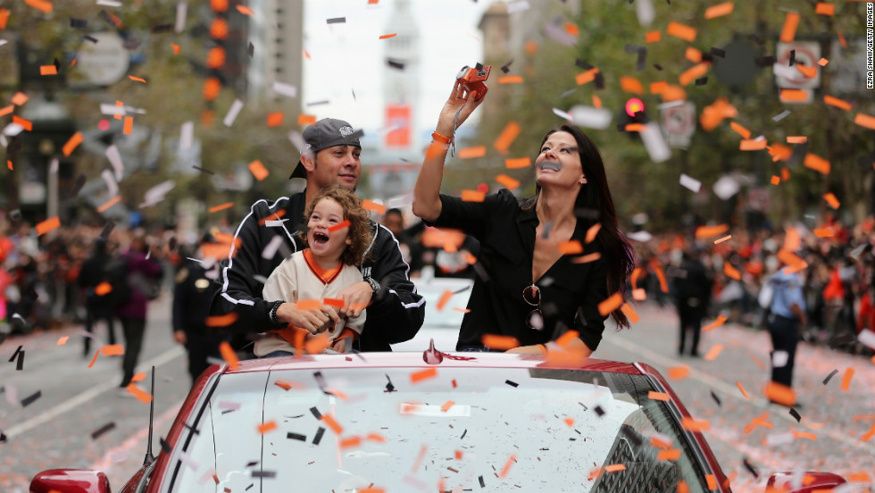 Giants pitcher Ryan Vogelsong rides in the parade with his wife and son.