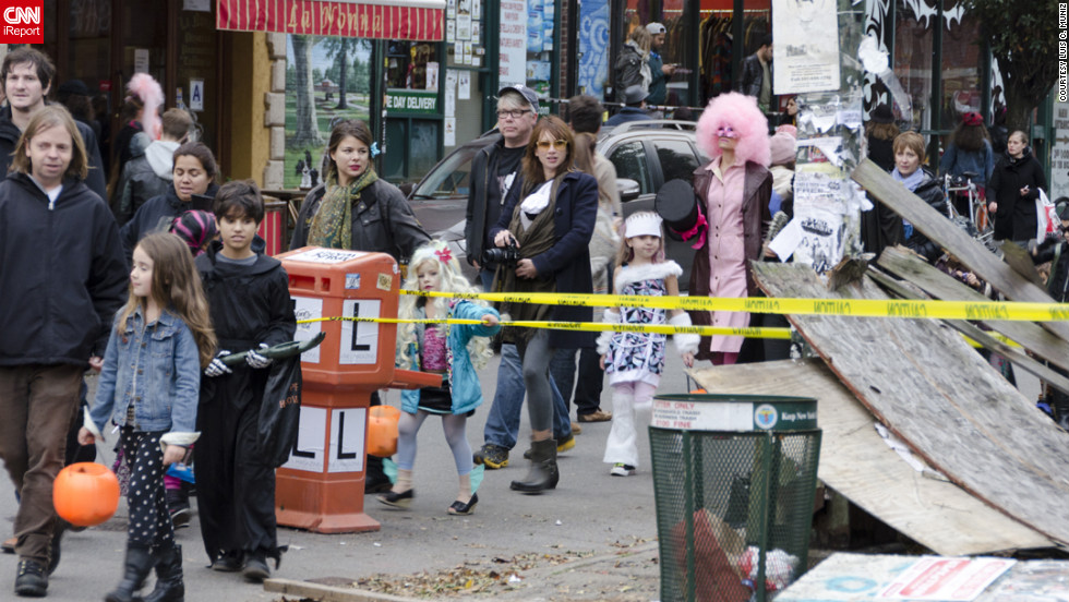 "<a href=""http://ireport.cnn.com/docs/DOC-869953"">Luis C. Muniz</a> snapped this photo of trick-or-treaters in Brooklyn making their way amid damage brought on by Superstorm Sandy."
