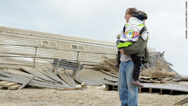 A man carries his daughter as they view Sandy's damage to a New Jersey boardwalk and beach area.