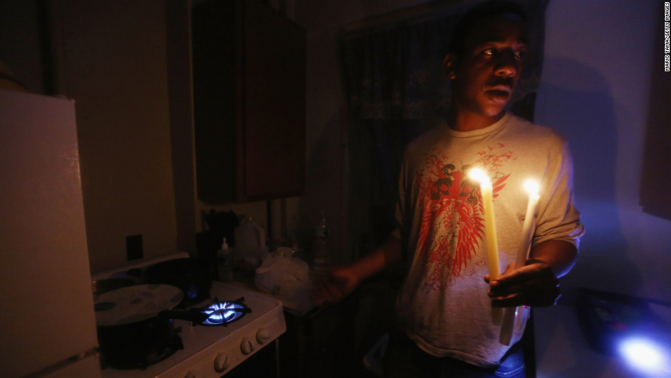 Geronimo Harrison's apartment in the East Village remains without power or water Thursday. He's using candles for light and a gas stove for heat.