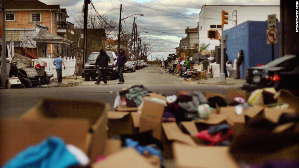 People gather among debris from Superstorm Sandy and boxes of donated goods on Saturday in Rockaway Beach.