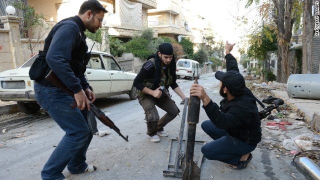Syrian rebel fighters set a home made rocket in Aleppo's northern Izaa quarter, on November 3, 2012.