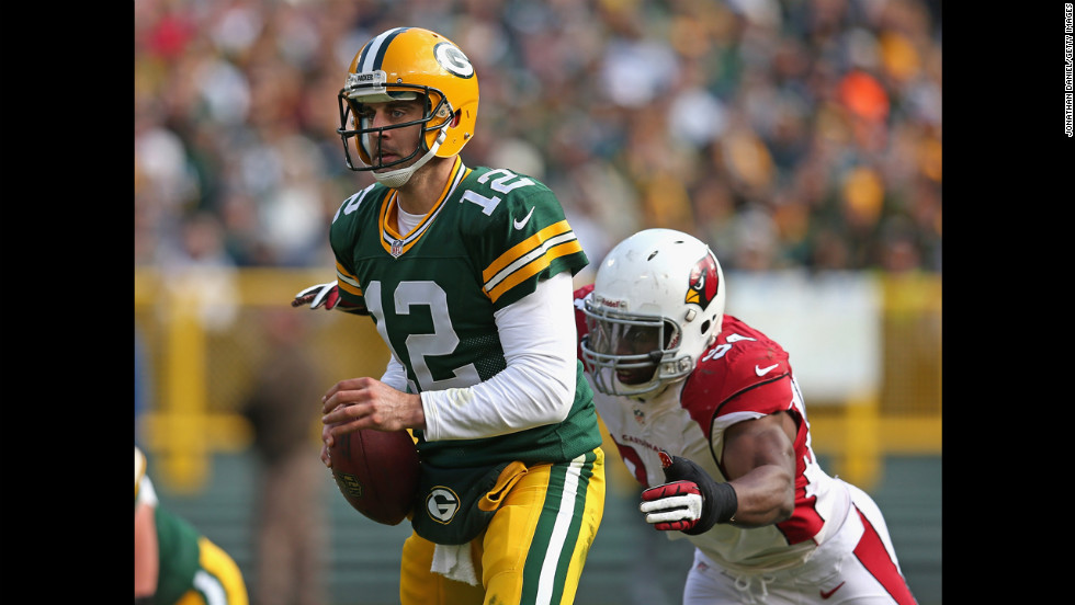 Aaron Rodgers of the Packers escapes from Sam Acho of the Cardinals on Sunday.