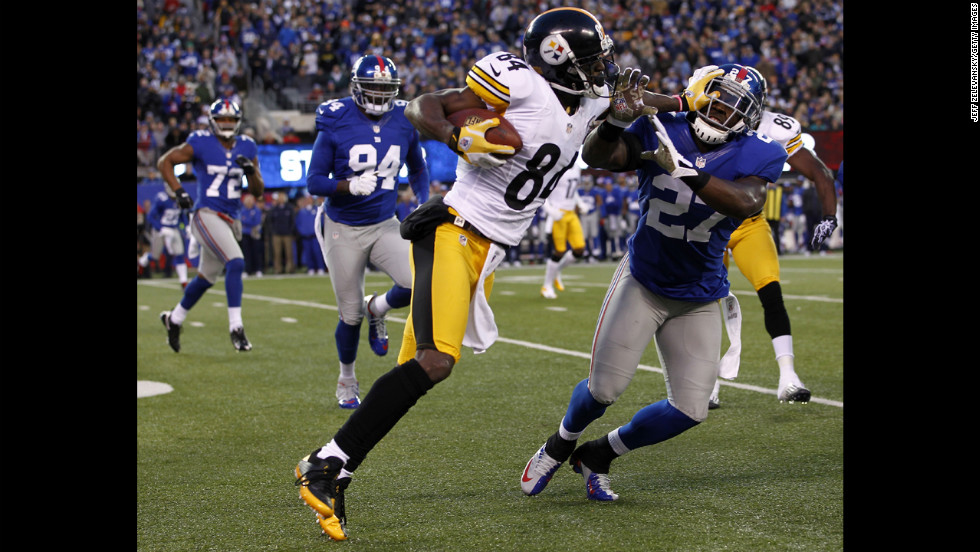 The Steelers' Antonio Brown fends off Stevie Brown of the Giants.