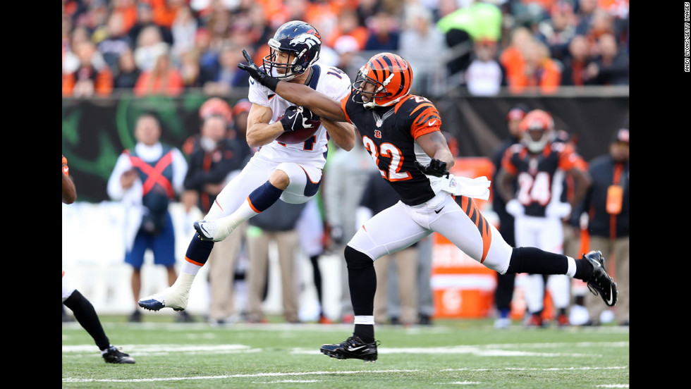 Brandon Stockely of the Broncos catches the ball while defended by Nate Clements of the Bengals on Sunday.