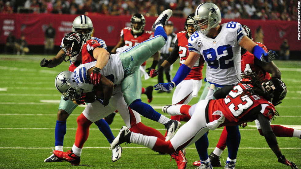 Lance Dunbar of the Cowboys is tackled by Falcons defenders Sunday night.