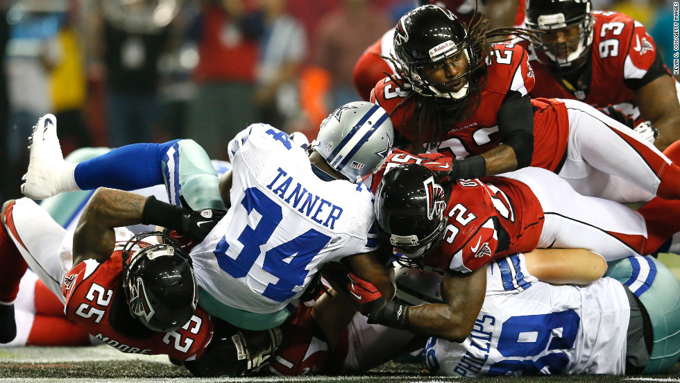 Phillip Tanner of the Cowboys is stopped short on a third down Sunday against the Falcons.