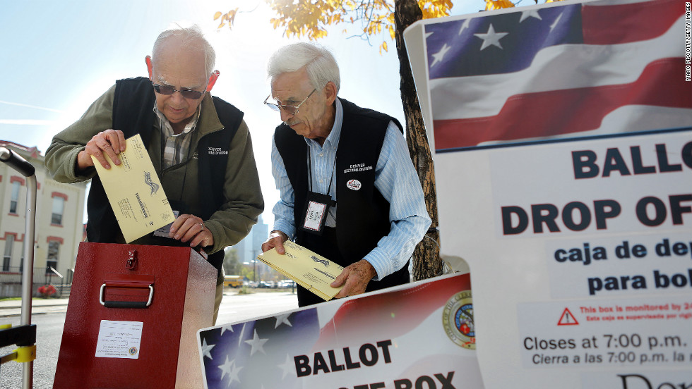 Election judges William Moeller, left, and Harry Sabin transfer ballots from a drop box outside of the library in Denver on October 22.