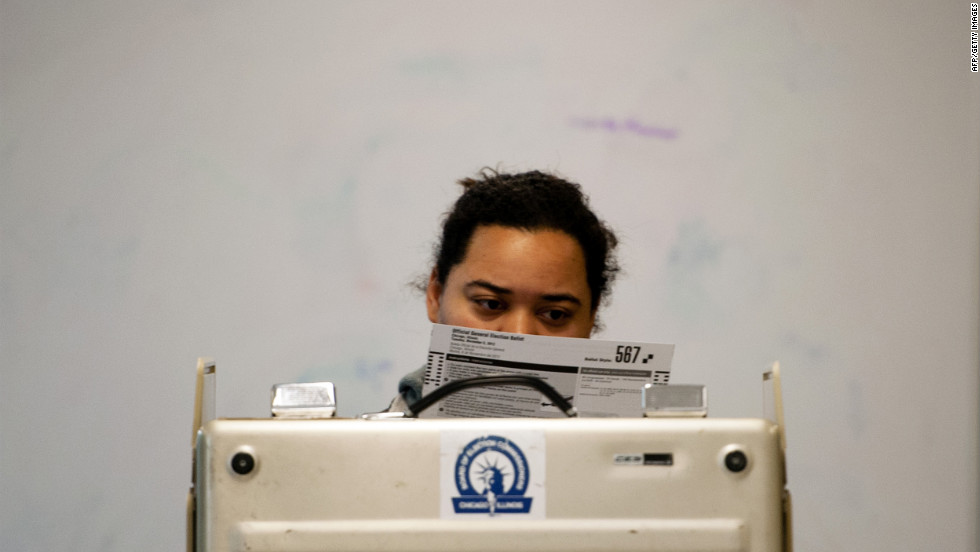 A voter takes a moment to read a paper ballot before casting her vote on Chicago's Northside.