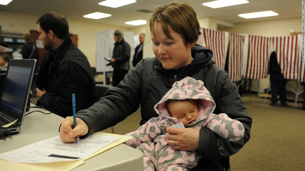 Kalli Hannafious holds her daughter Averie as she signs in for early voting in Anchorage, Alaska on October 2.