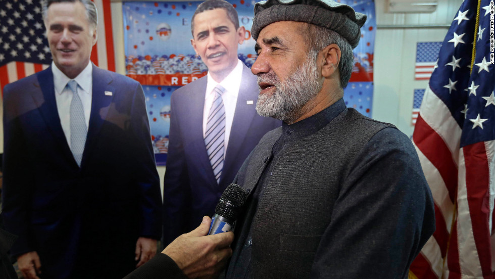 Afghan journalist Abdul hai Warshan is interviewed in front of cardboard cutouts of U.S. President Barack Obama and Republican presidential candidate Mitt Romney at the U.S. embassy in Kabul, Afghanistan.