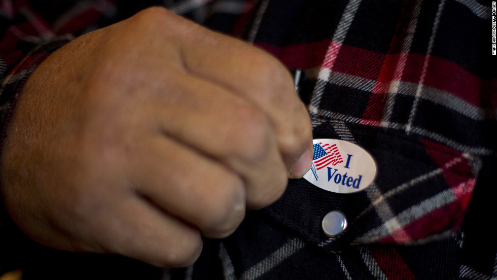 "A man puts on an ""I Voted"" sticker after casting his ballot in Otter Creek, Iowa, on Tuesday."