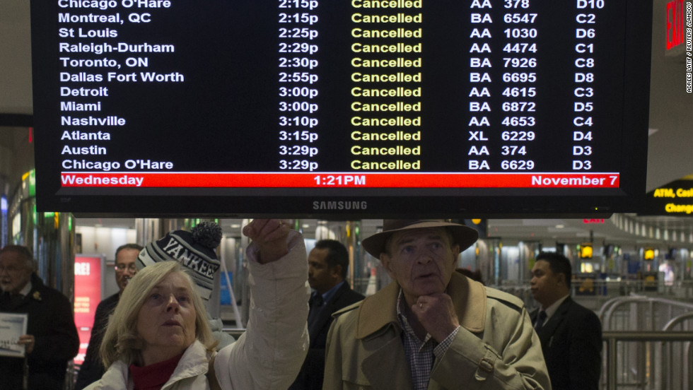 Travelers check a list of canceled flights in New York's LaGuardia Airport on Wednesday.