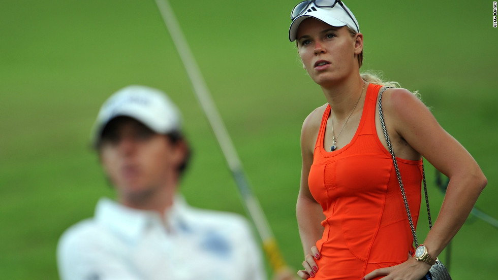 Caroline Wozniacki watches boyfriend Rory McIlroy during the continuation of the weather-delayed first round of the Singapore Open.