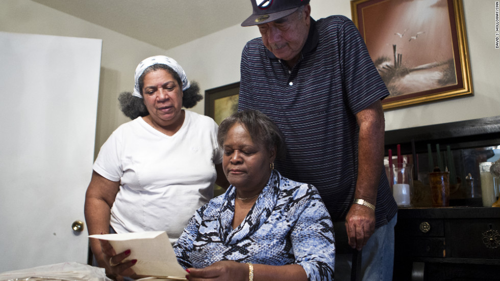 Sgt. Rodney Davis' sister, Debra Ray, standing, and brother Gordon Davis Jr. look at a letter with Gordon's wife, Josephine. The family has a collection of letters written by the Marine after he enlisted in 1961.