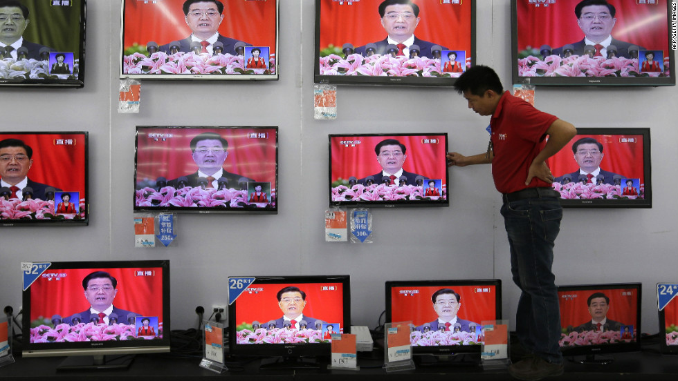 A man adjusts a television screen showing a live broadcast of Hu speaking at the Party Congress at a supermarket in Wuhan, Hubei province on November 8.