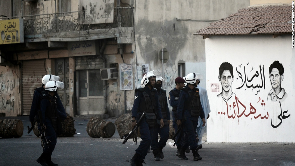 Bahraini riot policemen walk past graffiti reading in Arabic: 'Peace on our martyrs' as they try to disperse protesters. The teenager was killed as police attempted to stop pposition supporters from joining a mass during weekly Friday prayers.