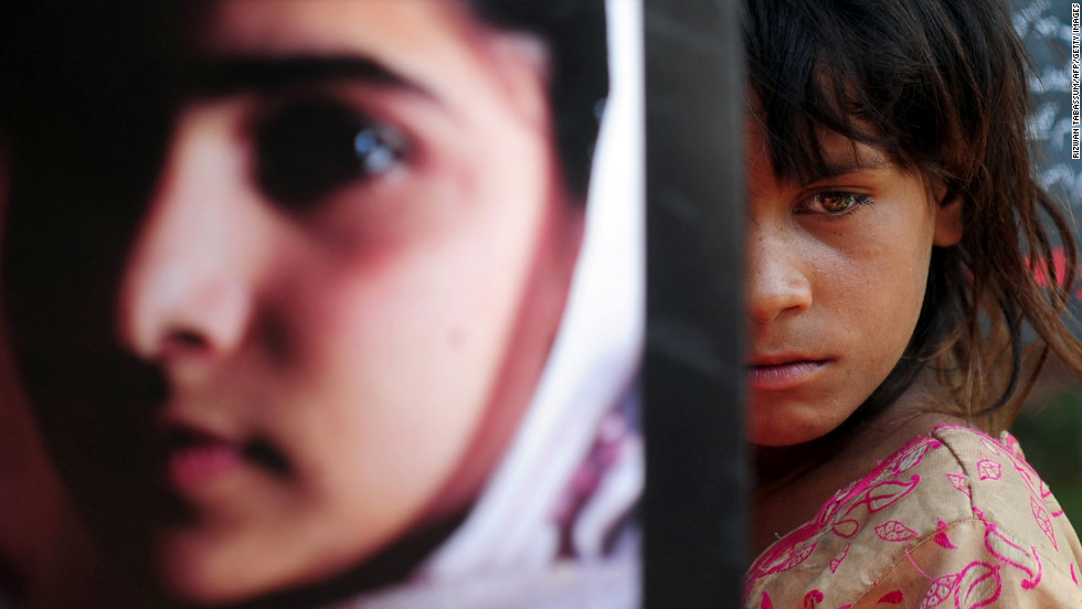 A Pakistani girl carries a photograph of Malala in Karachi to mark Malala Day.