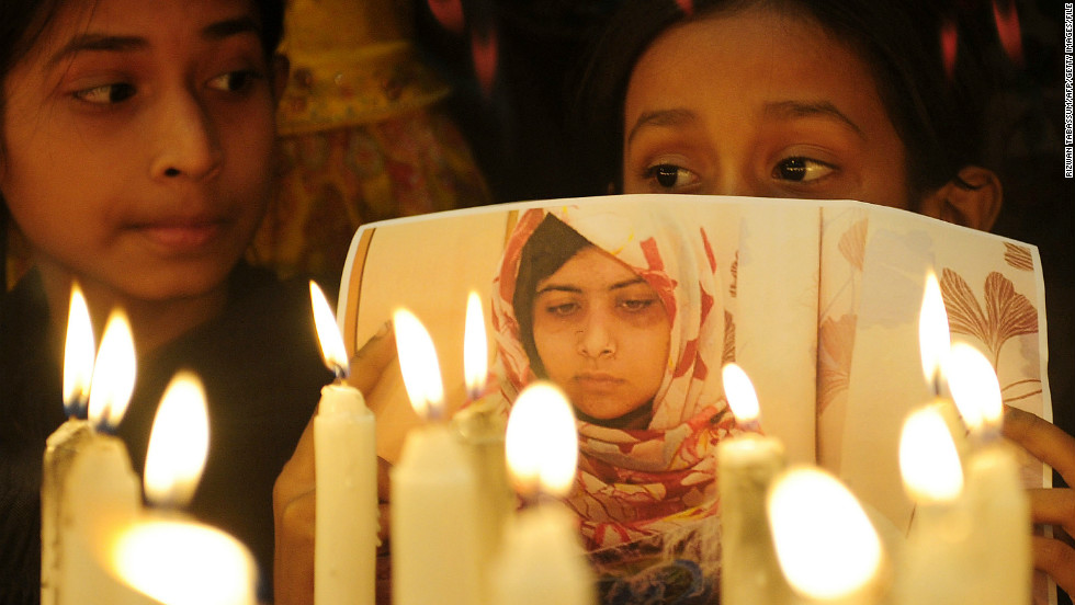 Pakistani supporters hold photographs of Malala as they stand alongside burning candles during a ceremony to mark Malala Day in Karachi on Saturday, November 10, 2012. The teen activist was shot in the head by the Taliban as she rode home from school in a van last month. She had defied the militant group by insisting on the right of girls to go to school. The attack has stirred outrage in Pakistan and around the world.