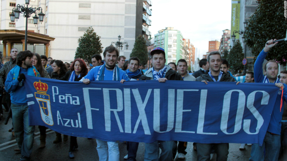 Real Oviedo fans hold up a banner as they march through the northern city on their way to the game.