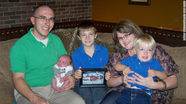 The Dykes family holds a photo of Jesse Ray, who was born prematurely and died in 2008.