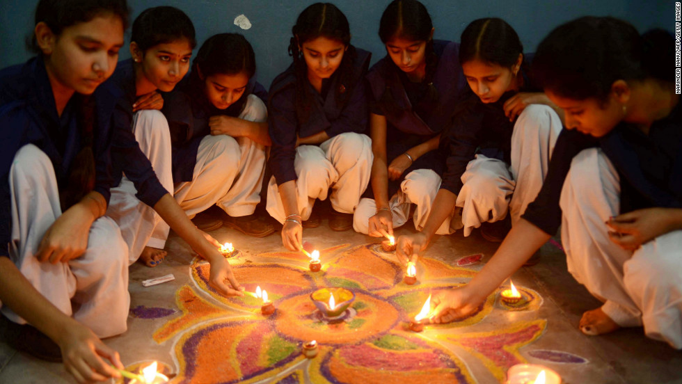 "Schoolgirls gather near a ""Rangoli,"" a pattern made from colored powder, ahead of Diwali celebrations  at a school in Amritsar, India, on Monday."