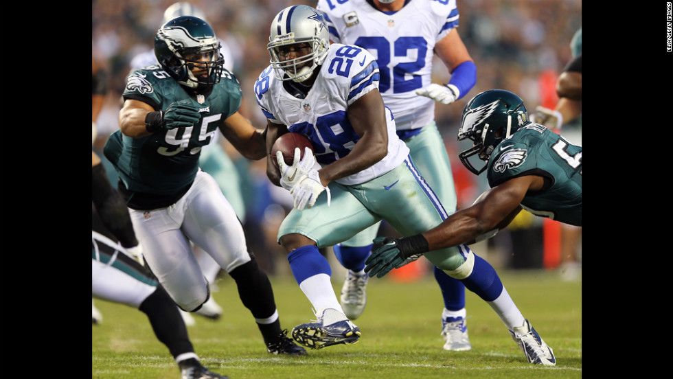 Felix Jones of the Cowboys carries the ball as Mychal Kendricks and DeMeco Ryans of the Eagles defend on Sunday.