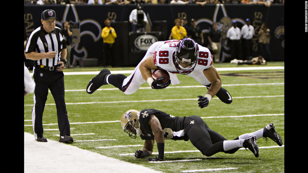 Tony Gonzalez of the Atlanta Falcons dives over Jabari Greer of the New Orleans Saints at Mercedes-Benz Superdome on Sunday in New Orleans.
