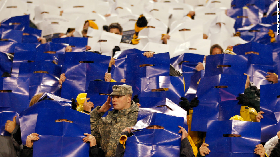 A member of the military stands at attention as fans hold up colored posters that made up the colors of the American flag during the performance of the national anthem before the Steelers-Chiefs game on Monday. Veterans Day was on Sunday, November 11.