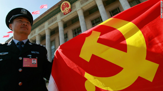 A Chinese policeman holds a Chinese Communist Party flag to show his supports to the party during the 17th Communist Party Congress in Beijing 15 October 2007.