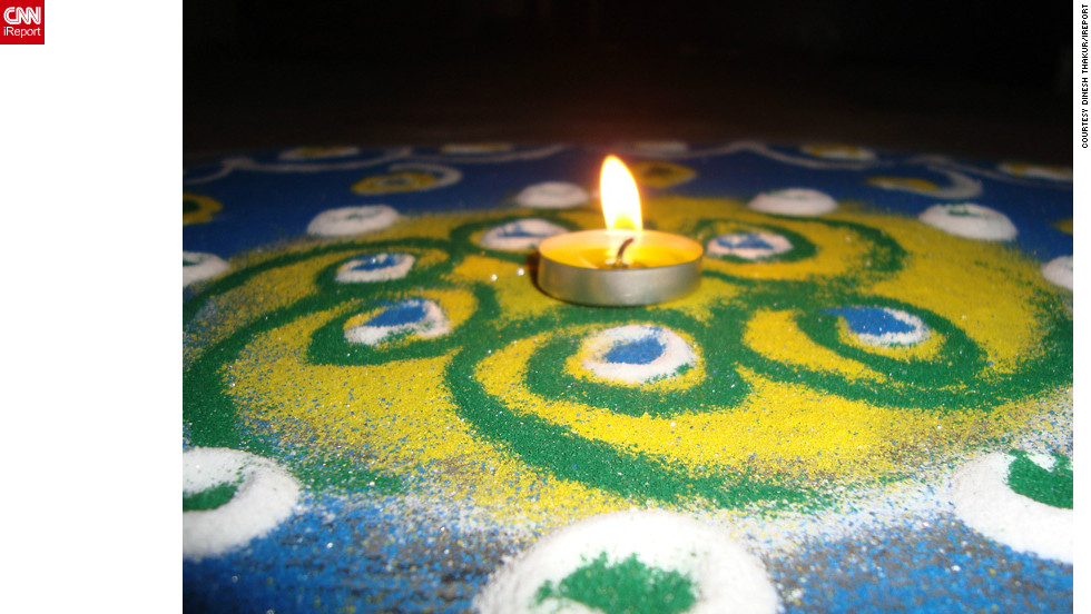 "Diwali is a festival that provides the opportunity to celebrate life with colors as well as lights, says <a href=""http://ireport.cnn.com/people/deadspirit6"">Dinesh Thakur</a> of Pune, India. ""It symbolizes victory of good over evil - light defeating darkness. It teaches us to have faith in the 'good' and not give into the darkness,"" he adds. He took this image of a single candle resting above a rangoli artwork to mark the start of this year's festival."