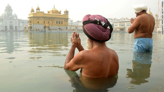 Indian Sikh devotees offer prayers as they stand in the holy sarover (water tank) at the Golden Temple in Amritsar on November 13, 2012, on the ocassion of Bandi Chhor Divas or Diwali. Sikhs celebrate Bandi Chhor Divas or Diwali to mark the return of the Sixth Guru, Guru Hargobind Ji, who was freed from imprisonment and also managed to release 52 political prisoners at the same time from Gwalior fort by Mughal Emperor Jahangir in 1619. AFP PHOTO/NARINDER NANU        (Photo credit should read NARINDER NANU/AFP/Getty Images)